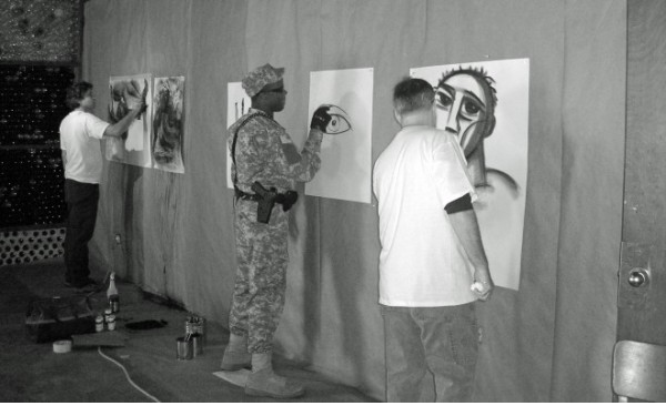 From the First Draw-a-thon in 2006. Draw-A-Thon founding organizers Brad Benischek and Kenny Harrison drawing with post-Katrina national guardsman.
